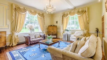 Large reception room with pale yellow walls, moulded details, ceiling rose and large sash windows