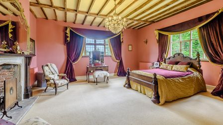 Large bedroom with double bed, timber beamed ceiling, hanging chandelier and huge feature fireplace