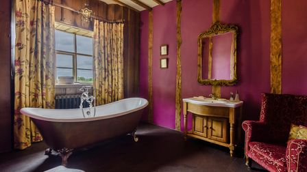 Burgundy coloured bathroom with freestanding claw-foot bath, velvet arm chair and baroque-style curtains