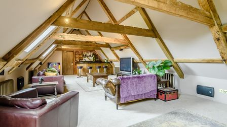 Large function room with sofa, TV, and wood panelled bar in the corner with taps, stools and vaulted beamed ceiling