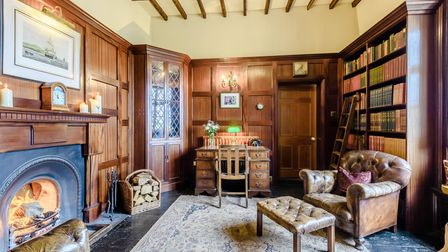 Wooden panelled study with timber ceiling, built-in bookcases, fireplace, leather armchair and desk