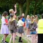 A large group of children and a woman with her hand in the air: Brownies on Rayne's new heritage trail