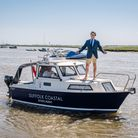 Smiling estate agent Tim Day in shorts on top of a small boat on River Alde, Suffolk
