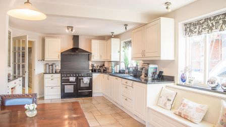 Open-plan kitchen with Shaker-style cabinets, range cooker with extractor over, tiled floor, large wooden table