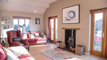 Large light-filled reception room with inset wood burner and wooden doors opening to patio terrace