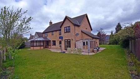 Rear view of large brick-built family home with lawn wraparound garden enclosed by wooden fencing