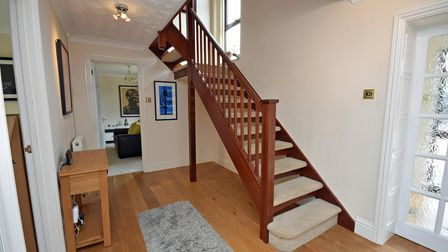 Inside the entrance hall to a property with a porch separated by frosted glass wall and a timber staircase