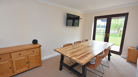 Dining area with large wooden table, wall-mounted TV and five 60s style chairs