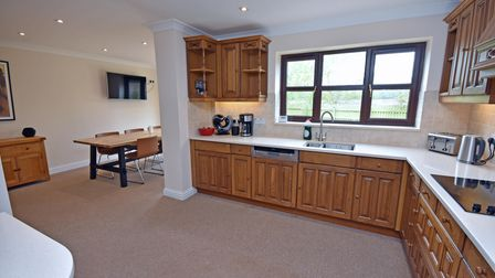 Kitchen/diner with wall and base pine units, white counter tops, inset electric hob