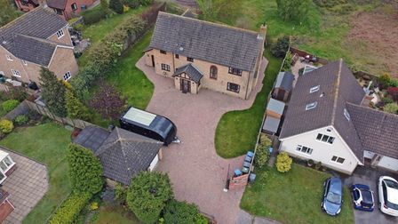 Aerial view of large brick-built family home with sweeping drive, double garage and caravan parked outside