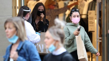 People wear a mask as they leave a shop amid the gradual lifting of restrictions to ease out of lock