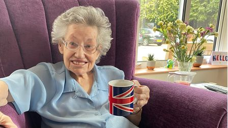 Picture of Westfields Care Home resident Cissie McHardy sitting in a chair with a mug in hand