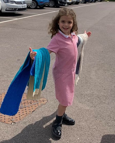 Darcie, 6, pupil at Roydon Primary School, was delighted to receive scarves knitted by residents at De Lucy House in Diss