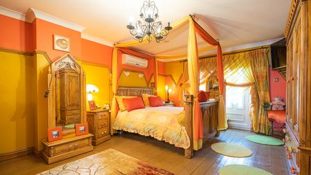 Large double bedroom with picture rails, four-posted bed, exposed wood floors and curtains