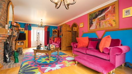 Colourful living room with bright pink walls, pink sofas, wood-effect floor and flower power-style rug on floor