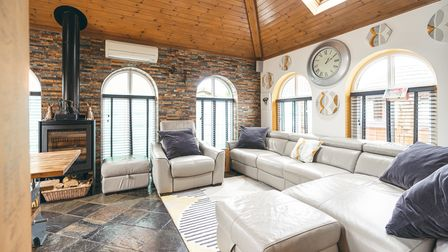 Light-filled 'loft'-style reception room with vaulted ceiling, exposed brick wall and arched windows