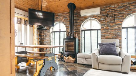 Modern loft-style reception room with exposed brick wall, panelled wooden vaulted ceiling, woodburner