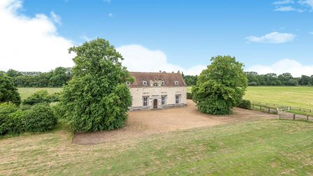 Large country house in the middle of the Norfolk countryside with blue skies and flat fields beyond