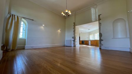 Large period-style reception room with huge ceilings, exposed brick, wood-effect floor and hanging chandelier