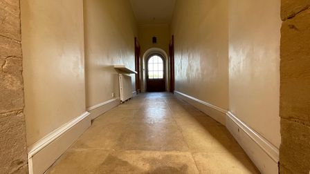 Long inner hall leading to a front door with glass window, stone floors