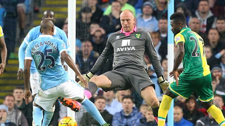 Norwich City keeper John Ruddy tries to recitfy his mistake by closing down Manchester City's Fernan