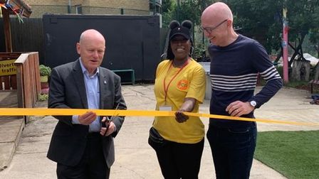 Mayor John Biggs cuts through the red tape, or yellow in this case, to get the playground up and running
