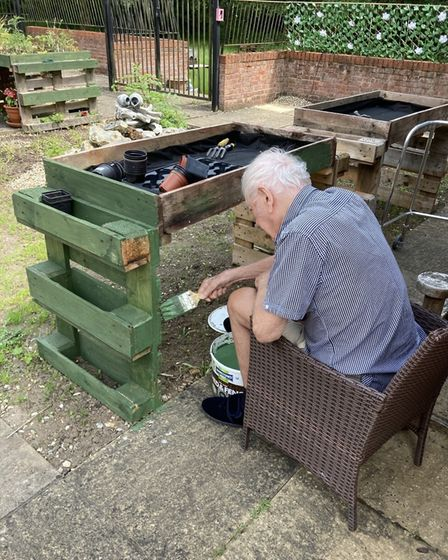 A resident paints one of the planter benches