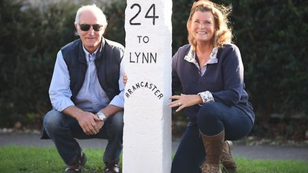 Martin and Marian Skillings with the milestone at Brancaster Staithe. Picture: Ian Burt