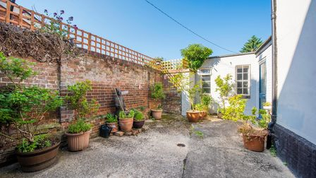 Courtyard garden with brick wall, trellis, white washed wall side of pub