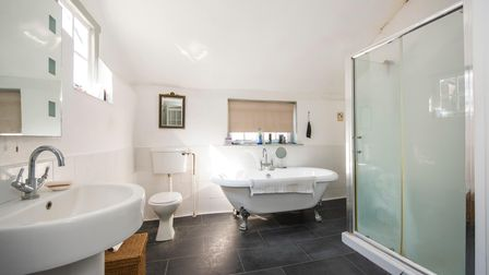 Huge modern bathroom with freestanding roll-top bath, double shower cubicle