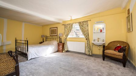 Large double bedroom with white painted walls, high ceilings, wrought iron bed and wicker armchair