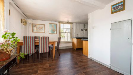 L-shaped kitchen/diner with table pushed up against a white wall, sash windows, wood flooring