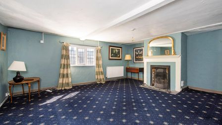 Large reception space with pub-style navy blue carpet, inglenook fireplace with open fire and small sash windows