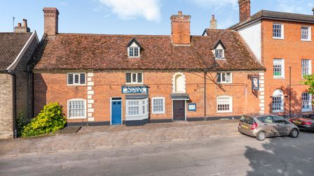 Aerial view of brick-built former pub set back from the road off a quiet village high street