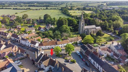 Aerial view of Woolpit, Suffolk, with a bright red arrow graphic pointing to a brick-built pub building