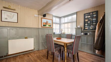 Corner of dining area with sage-green coloured panelled walls, wooden floors and dining table and chairs to seat four