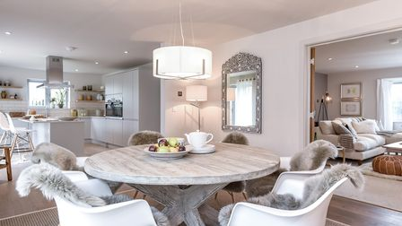 Contemporary open-plan living area with huge modern kitchen, round dining table and hanging lamp