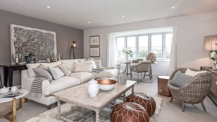 Modern neutral living area with sofa, coffee table facing window, stylish grey walls and abstract wall art