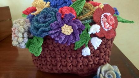 A hand-knitted basket of flowers by Barbara Lee for the Creation festival in Bedfield