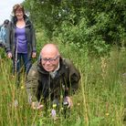 George Williams, front, taking a close look at some common spotted orchids, during one of the Norfol