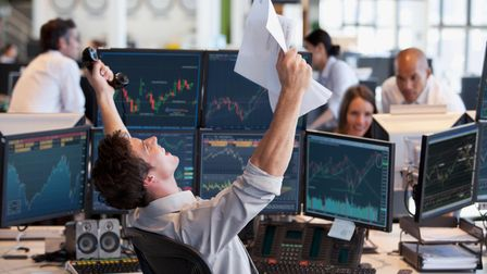 Young smartly dressed businessman holding phone and paperwork victorious in front of PC screens showing stocks