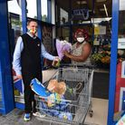Store manager Chris Pawson presnts a bouquet of flowers to the first customer through the door Oluke