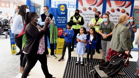 Staff at the new Lidl store, and local school children, applauding the first customers through the d