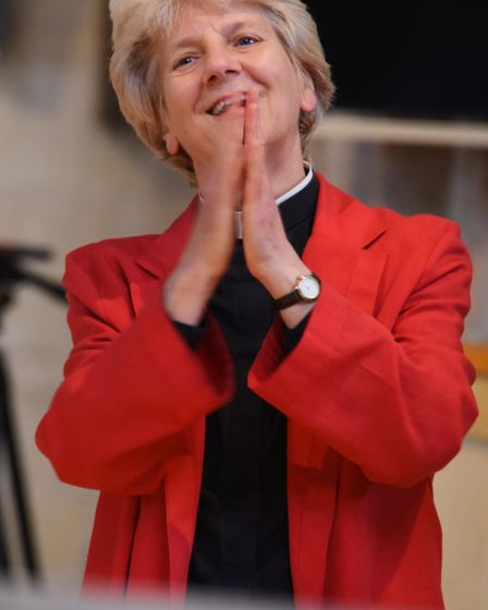 The Dean of Norwich, the Very Rev Jane Hedges, claps as the skull of Dippy the Diplodocus is put in