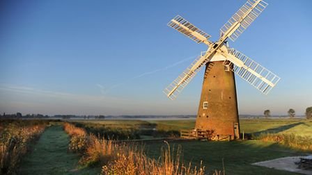 The autumnal colours are caught in the early morning golden sunlight over the River Yare on the Norf