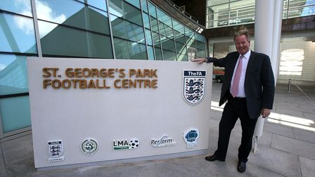 David Sheepshanks poses for photos outside the St George's Park Football Centre sign during a media