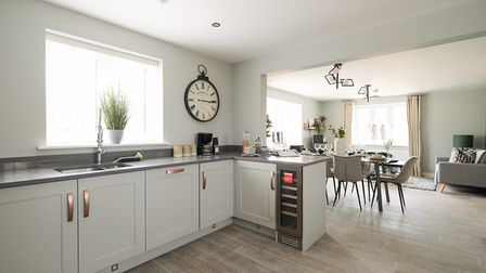 Sleek contemporary kitchen with base-level units, worktops and open-plan dining area with modern furniture