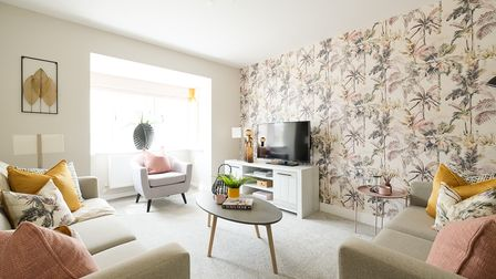 Light and airy living room with two sage-coloured fabric sofas, a console coffee table and tropical wallpaper
