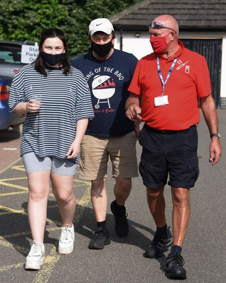 Marshall Terry Davies, right, escorts patient Emilia Riseborough and her dad, Barry, to their car as