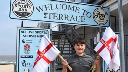 James Mayne with England flags at the entrance to The Terrace and sports bar at Claremont Pier in Lowestoft.